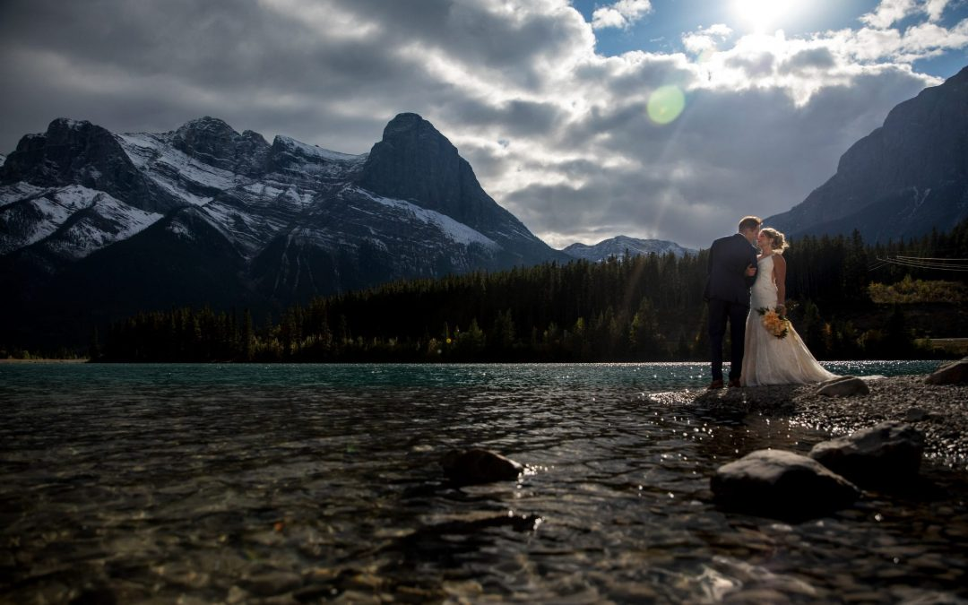 Bride and groom almost kissing by a lake in Canmore, Alberta with the mountains in the background